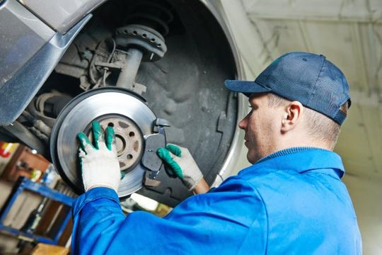 Car mechanic replacing brakes